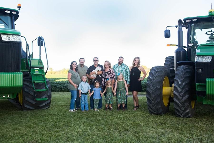 Stetzel family photo near their farm field and John Deere equipment