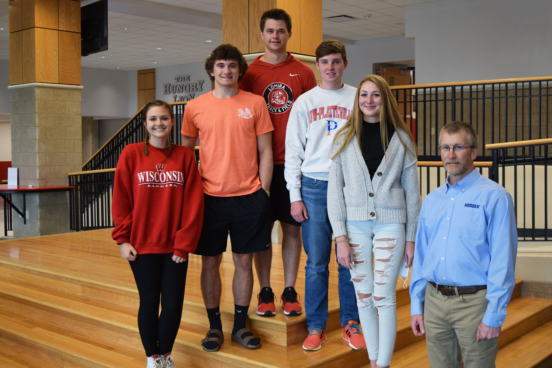 Five Lomira High School students standing on stairs with Kondex President Keith Johnson