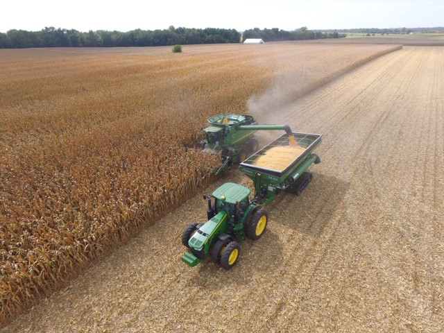 John Deere combine harvesting a large field of corn with grain cart collecting kernels